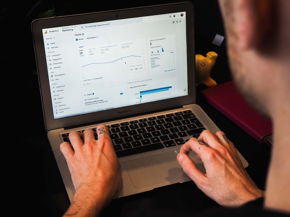 person using macbook pro on black table