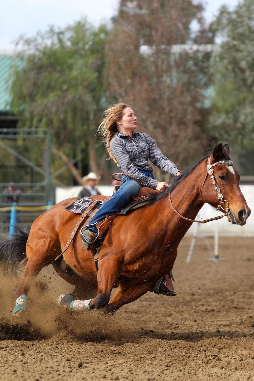 girl in blue denim jacket riding brown horse during daytime