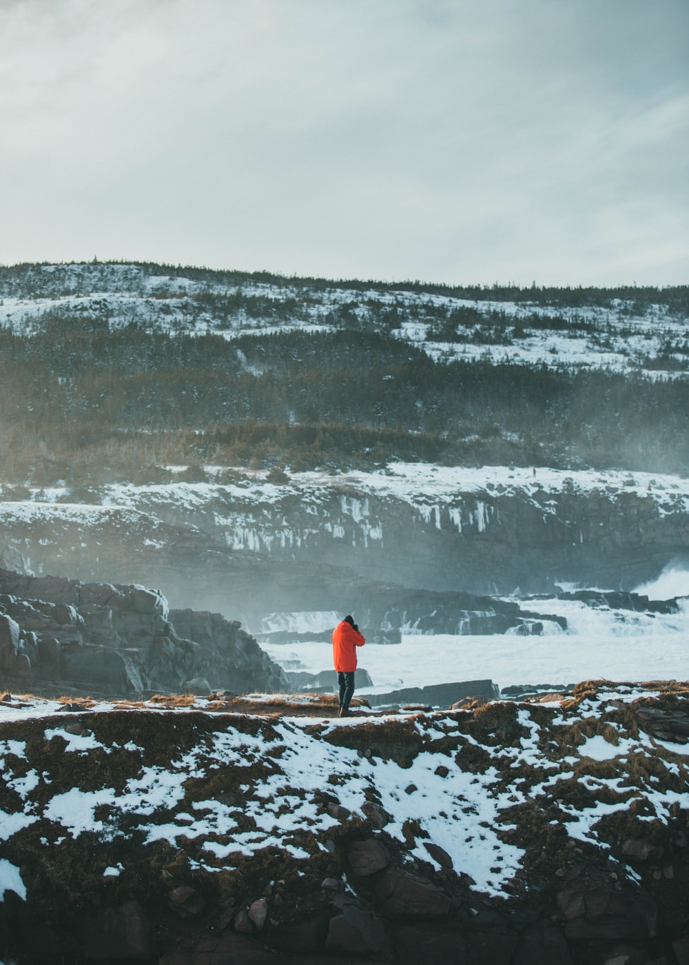person in red jacket standing on snow covered ground during daytime