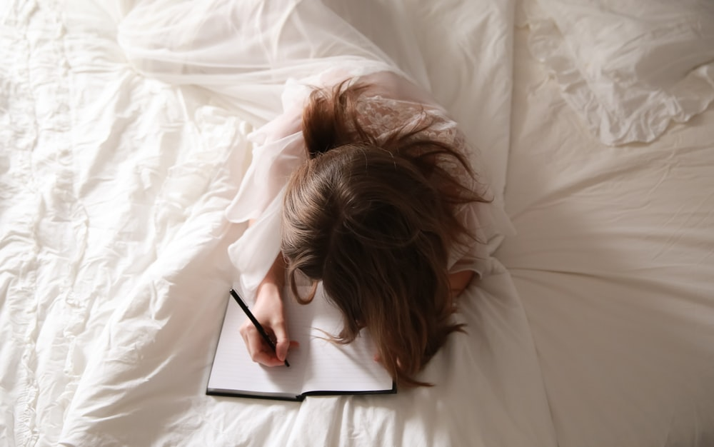 A photo of a woman writing in a journal lying on a bed