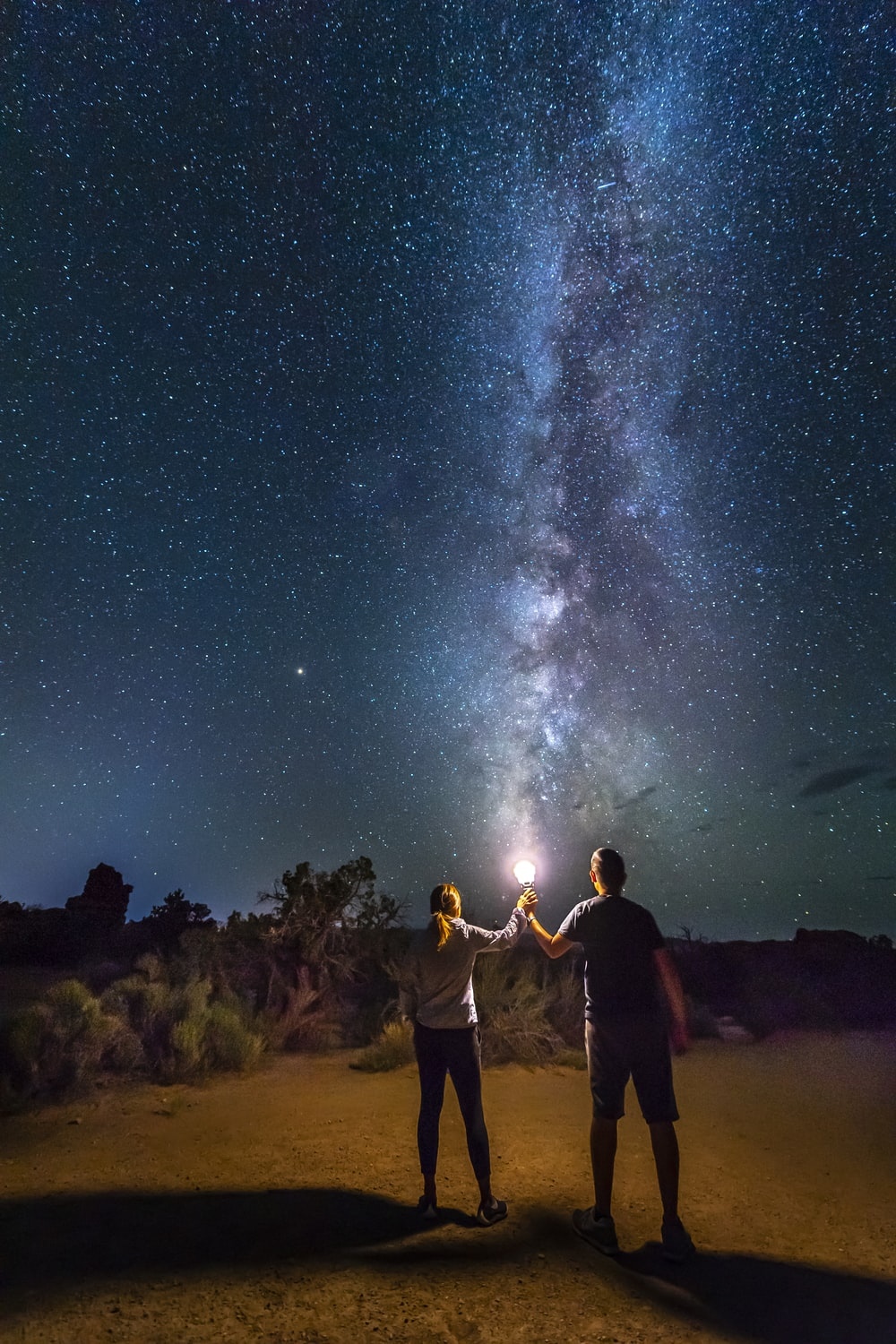 people standing on brown sand under starry night