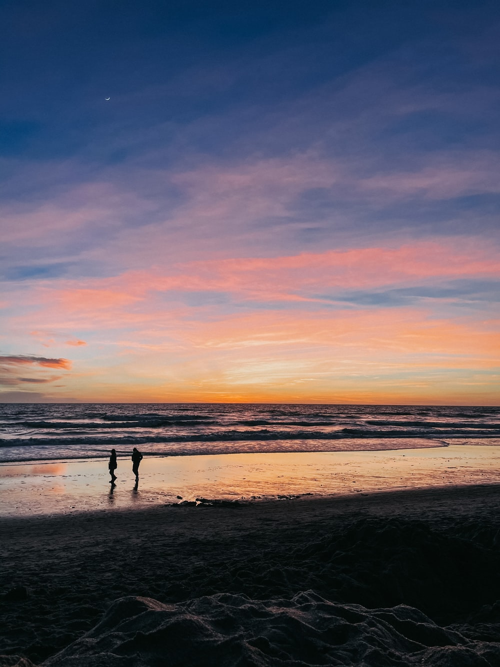 silhouette of 2 people walking on beach during sunset