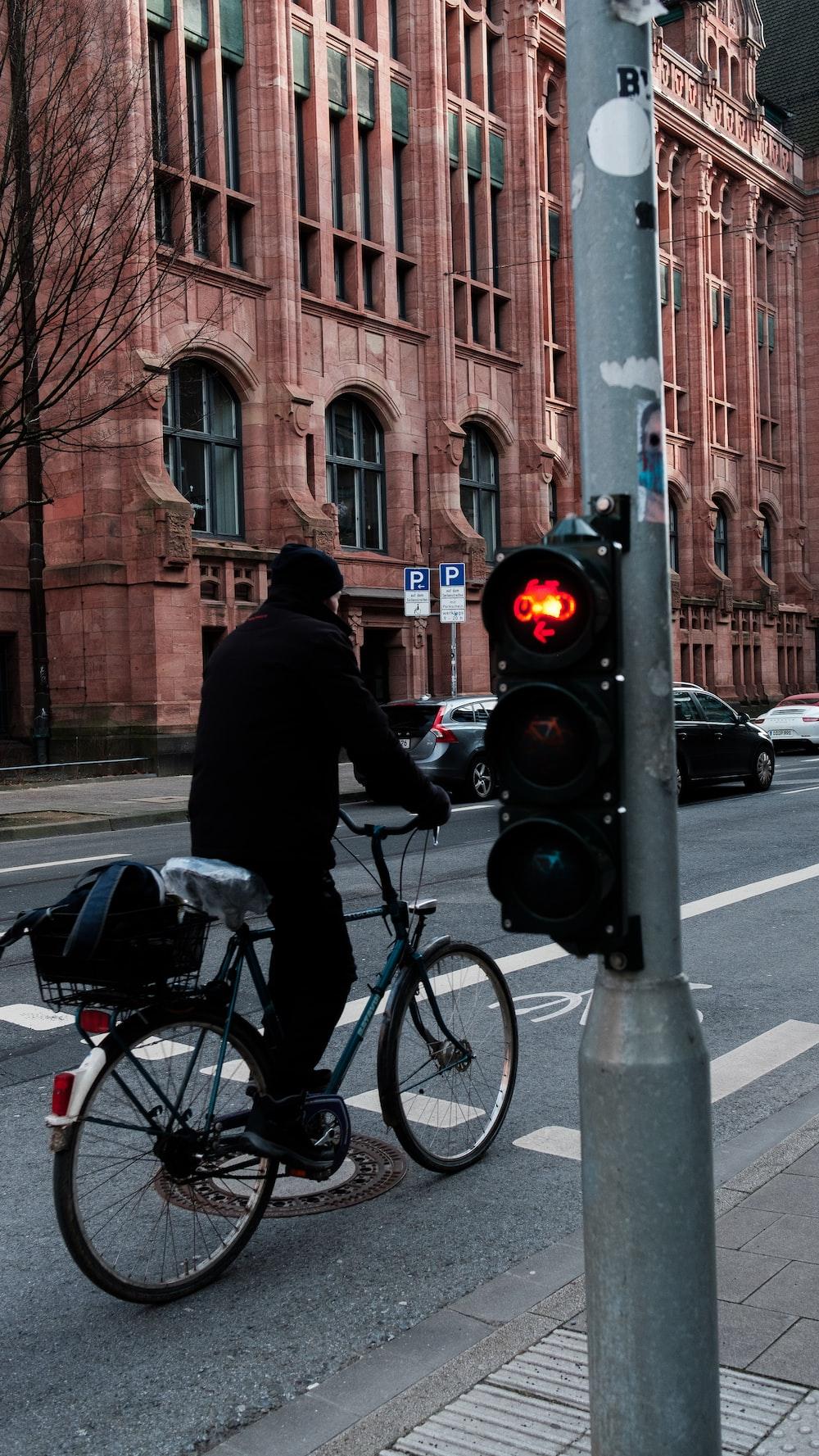 man in black jacket riding bicycle on road during daytime