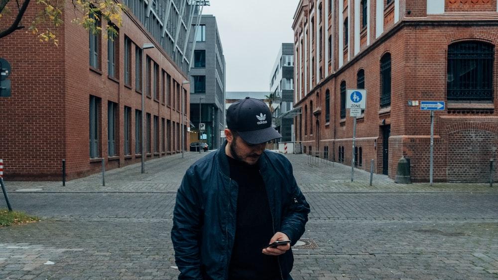man in black jacket and black cap standing on sidewalk during daytime