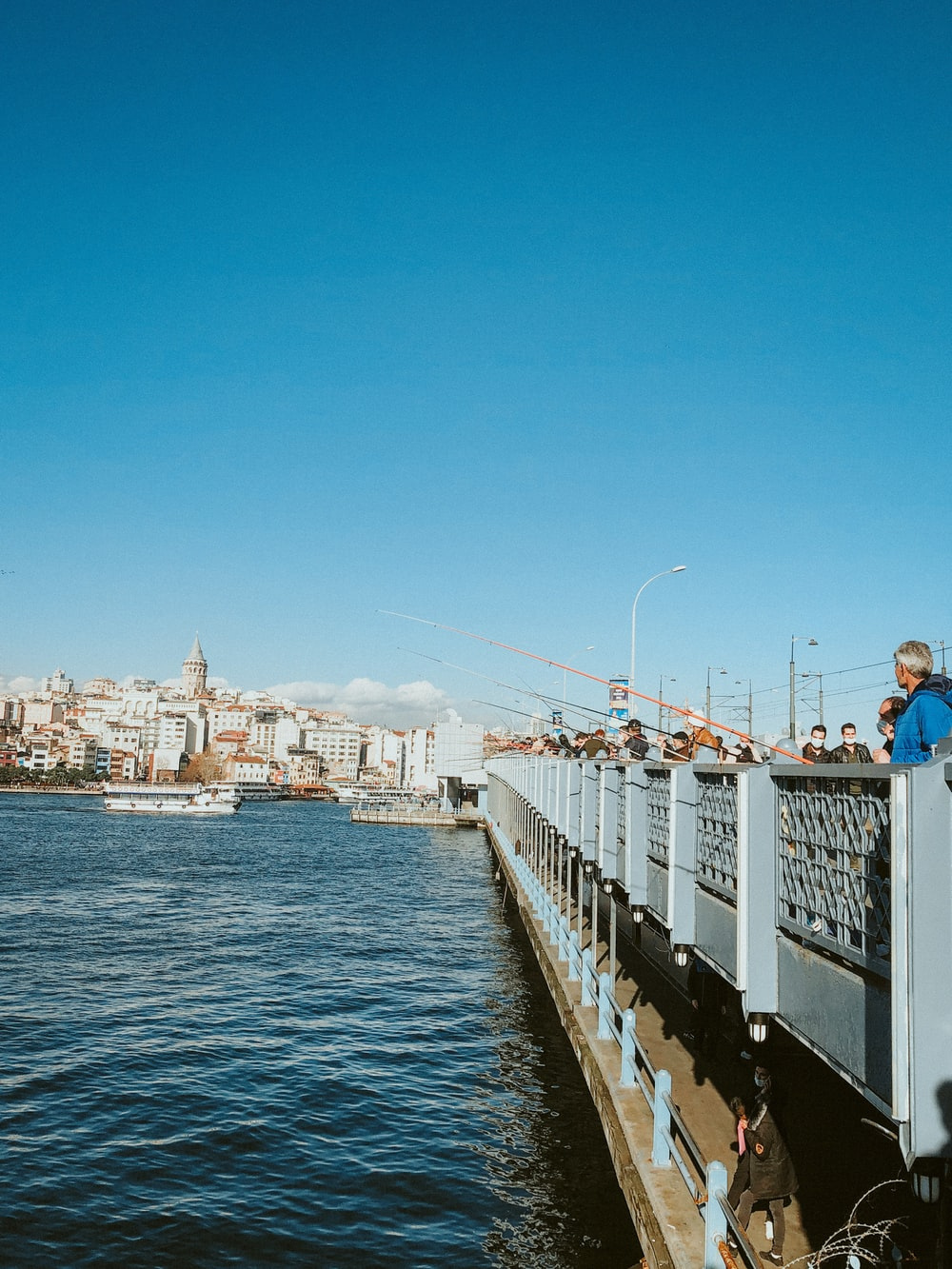 people on white and black bridge over blue sea during daytime