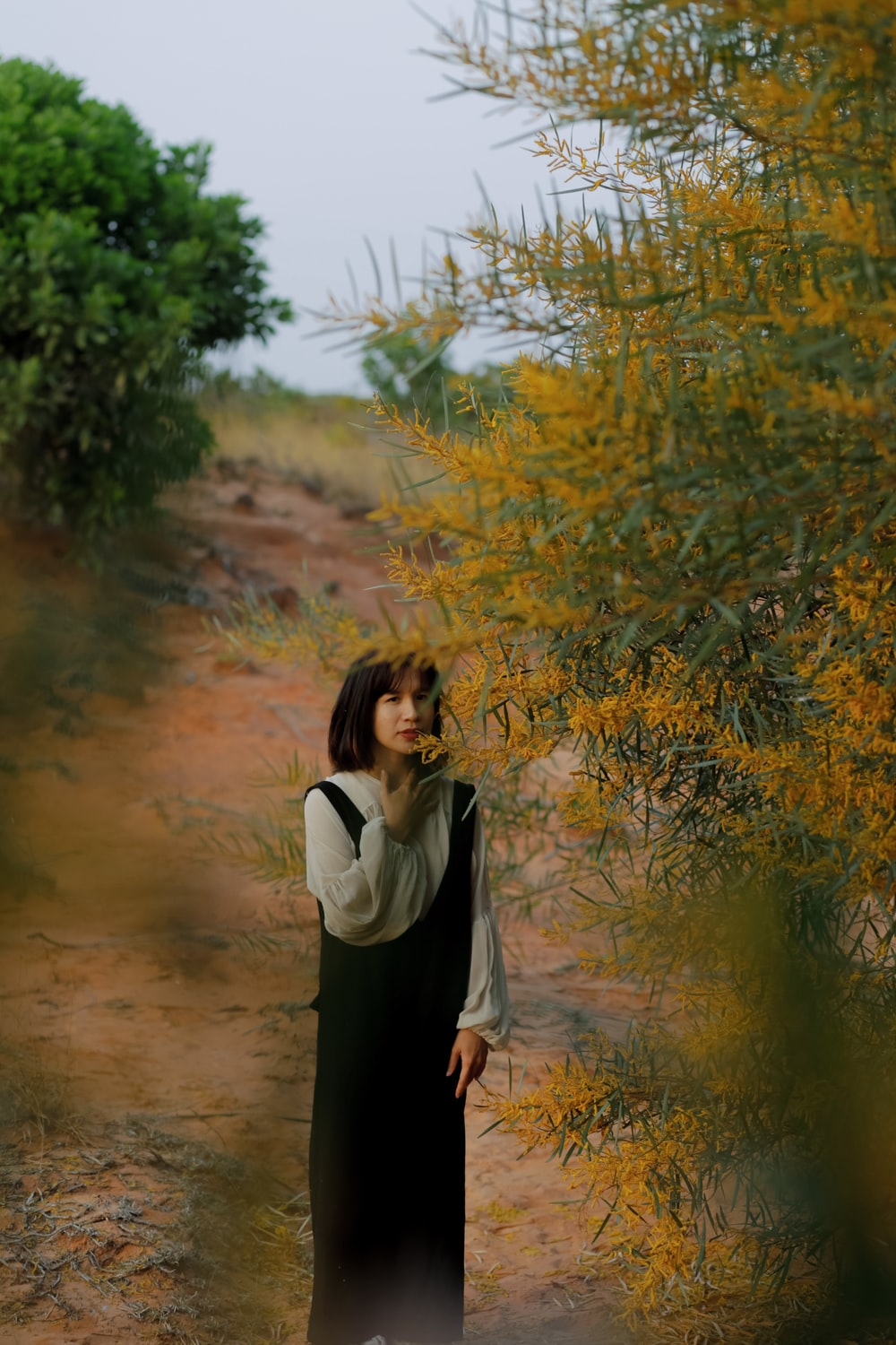 woman in white long sleeve shirt and black skirt standing near green tree during daytime