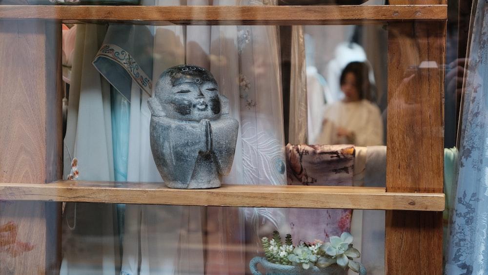 gray ceramic buddha figurine on brown wooden shelf