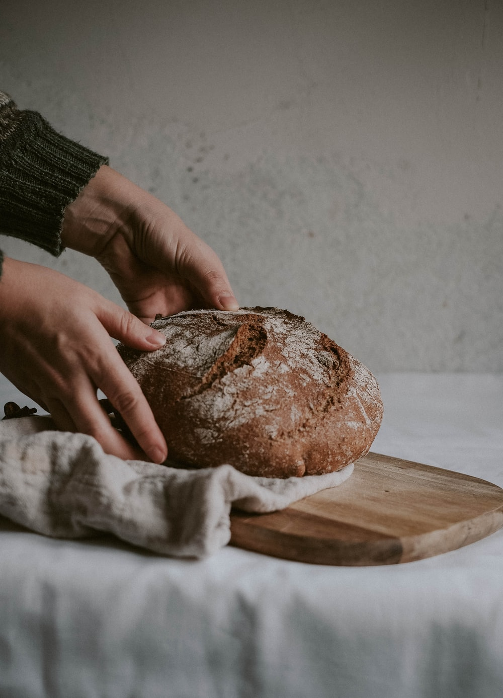 person holding brown bread on brown wooden chopping board