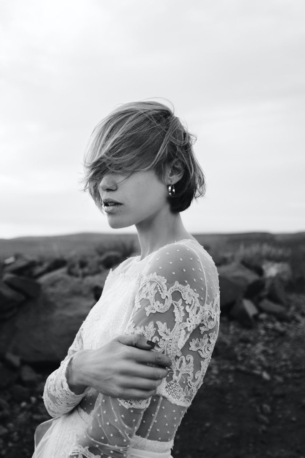 woman in white floral dress standing on rock formation during daytime