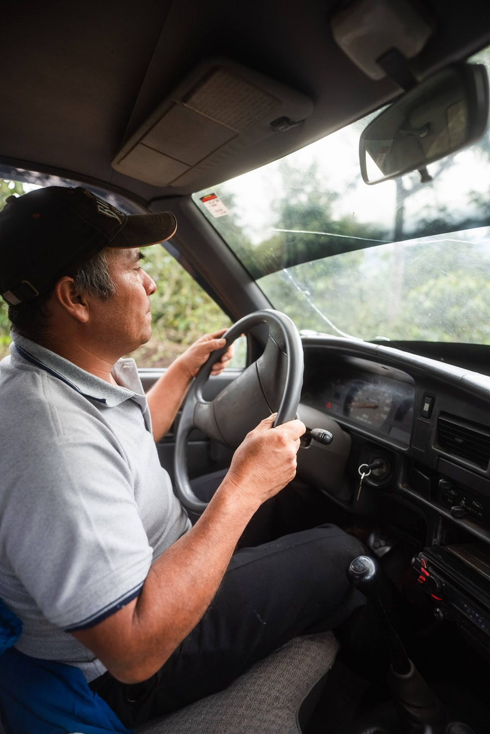 man in white polo shirt driving car during daytime