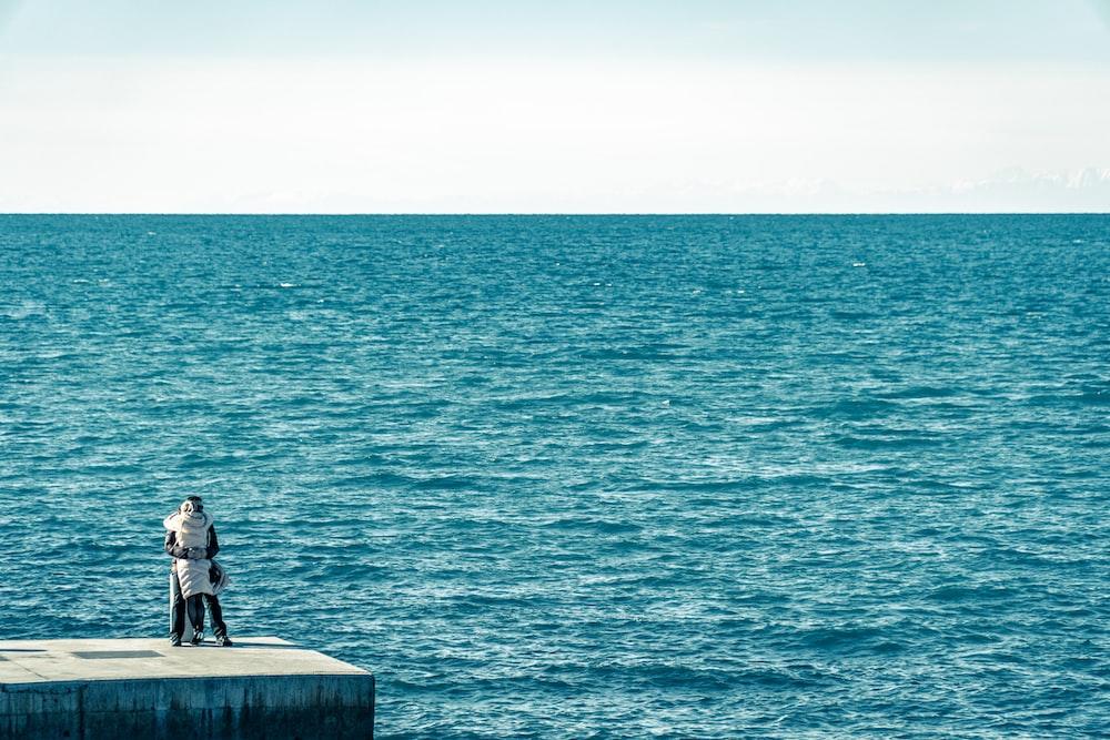 man in black jacket sitting on concrete bench near sea during daytime