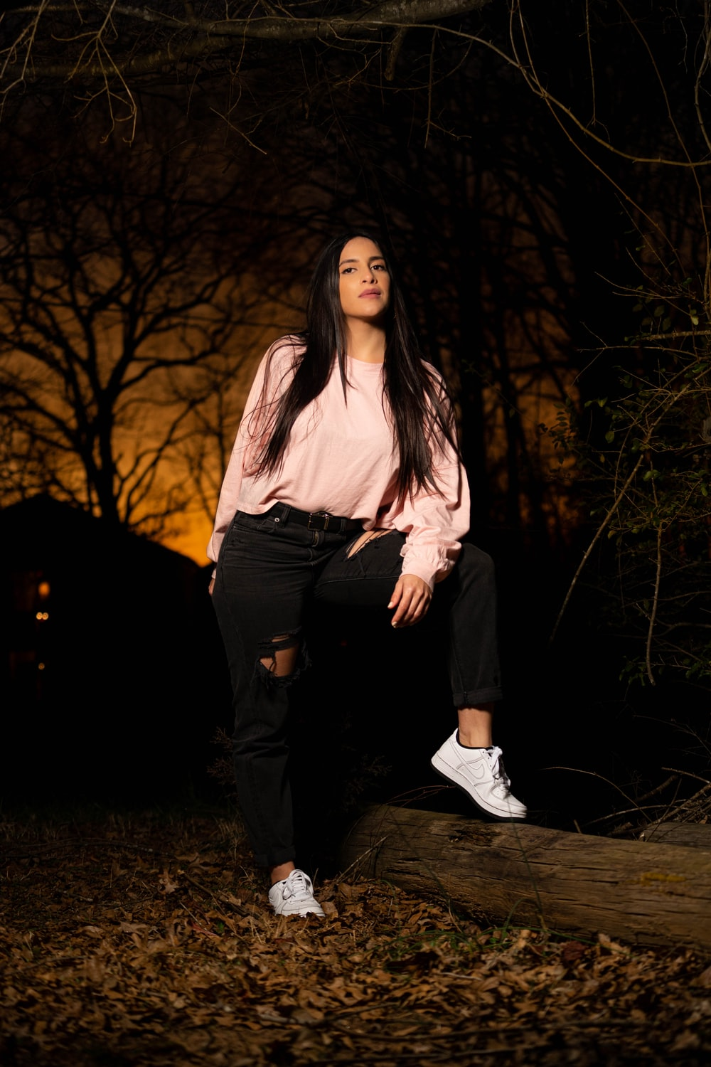 woman in white long sleeve shirt and black pants standing on forest during night time