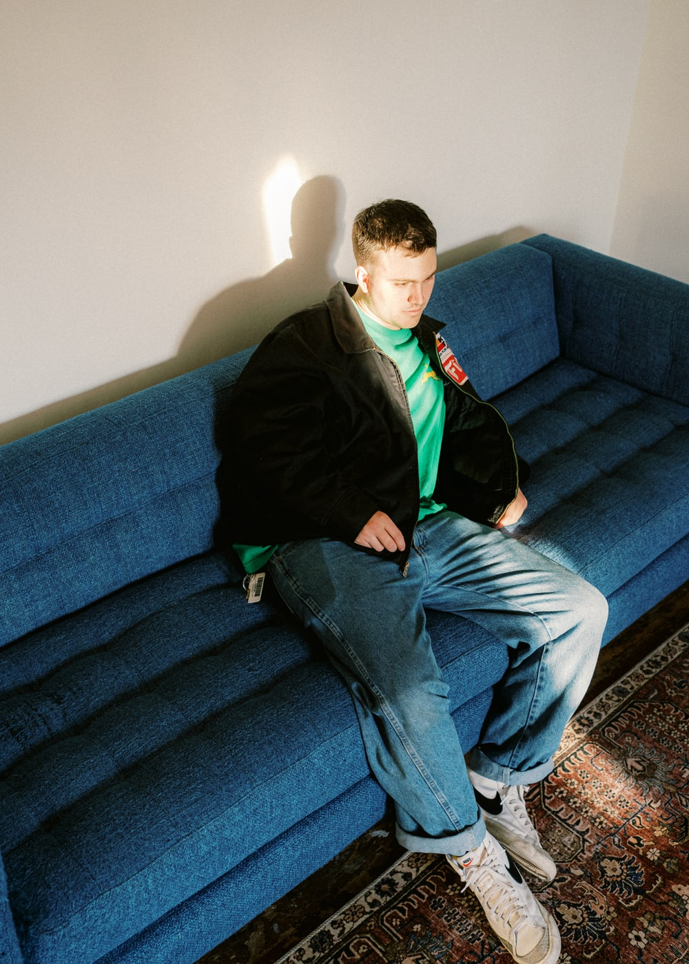 man in black jacket and blue denim jeans sitting on blue couch