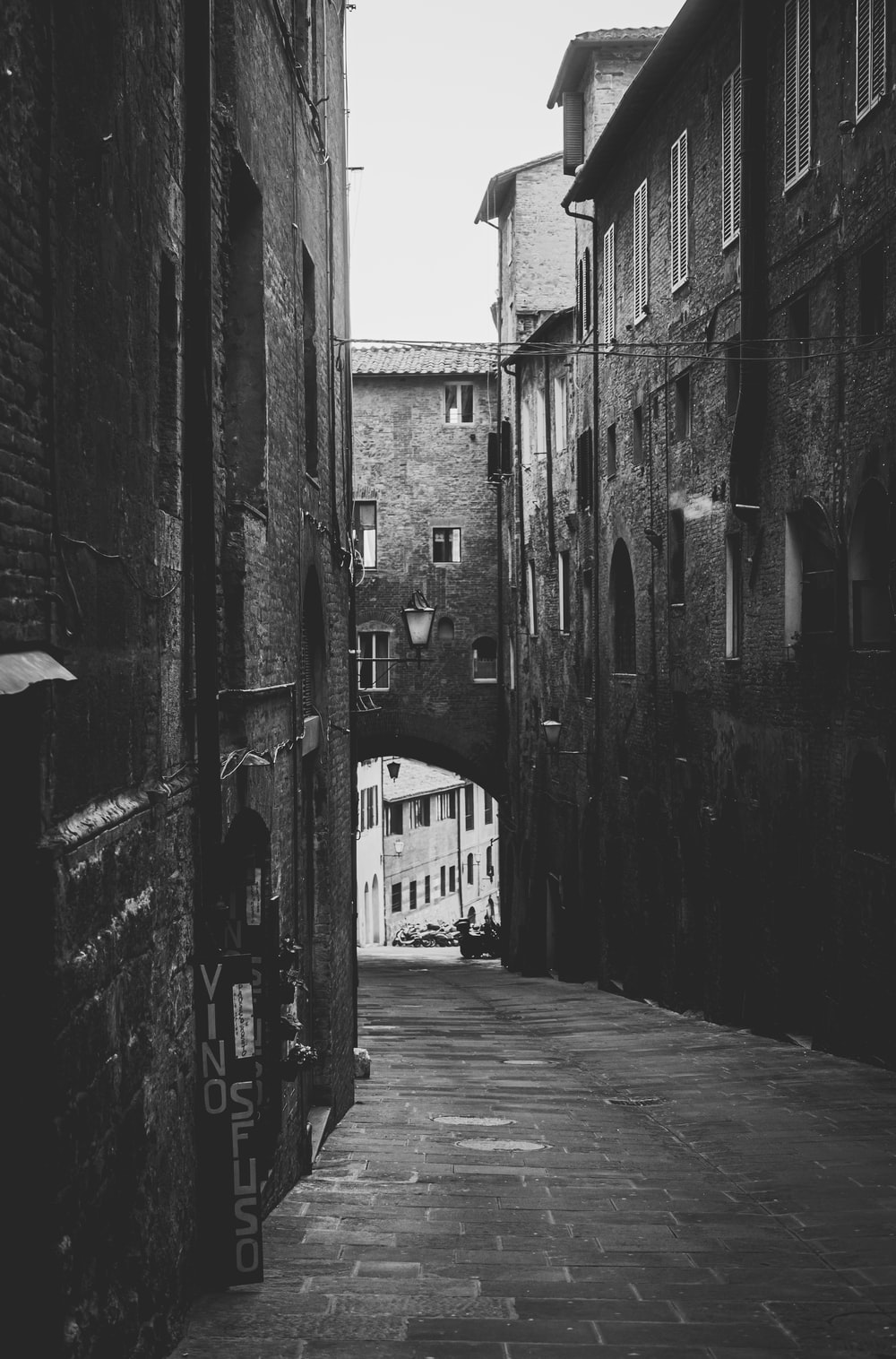 grayscale photo of alley between buildings