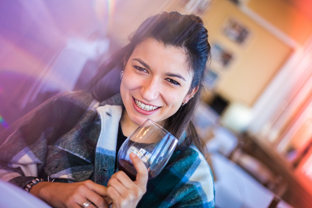smiling woman holding clear drinking glass