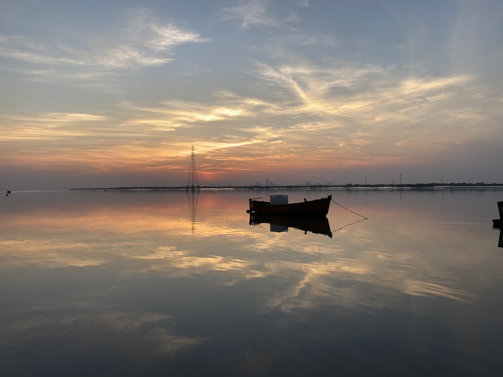 boat on calm sea during sunset