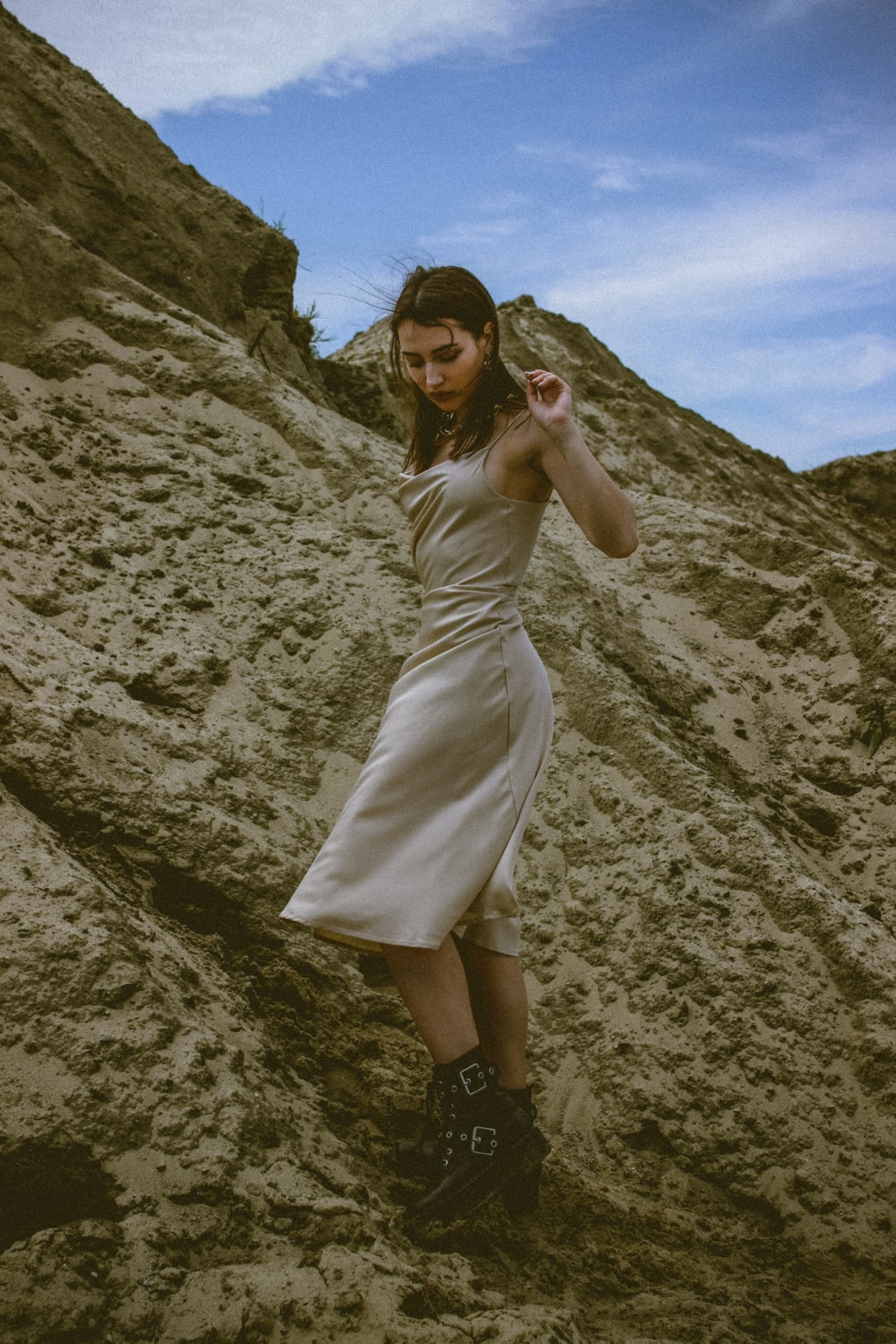woman in white dress standing on rocky hill during daytime