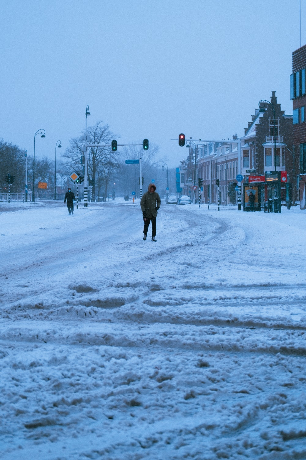 person in black coat walking on snow covered road during daytime
