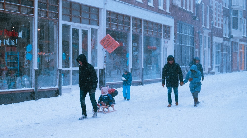 people walking on snow covered ground during daytime