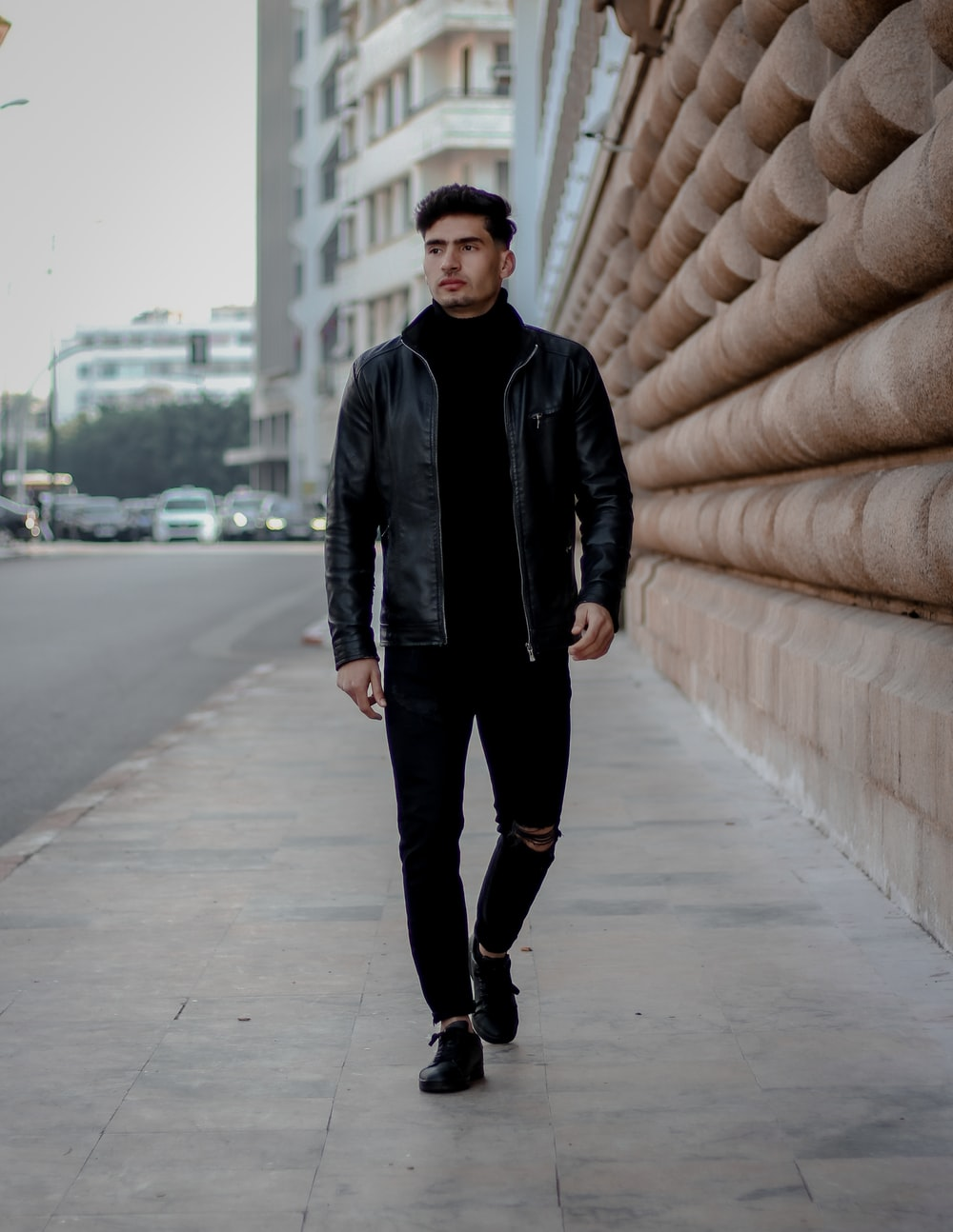 man in black leather jacket standing on sidewalk during daytime