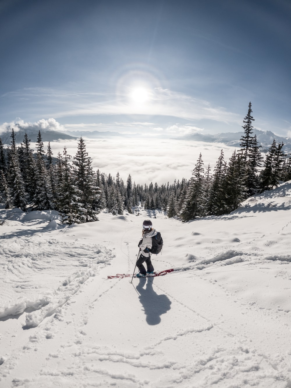 person in red jacket and blue pants riding ski blades on snow covered ground during daytime