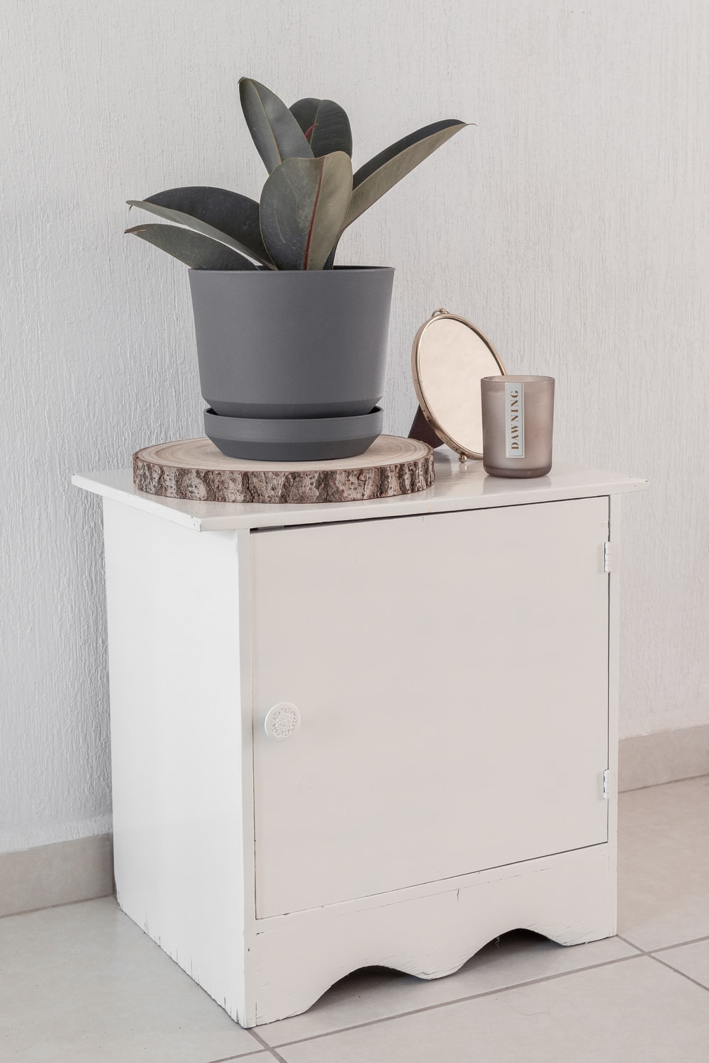 white and brown ceramic mug on white wooden cabinet