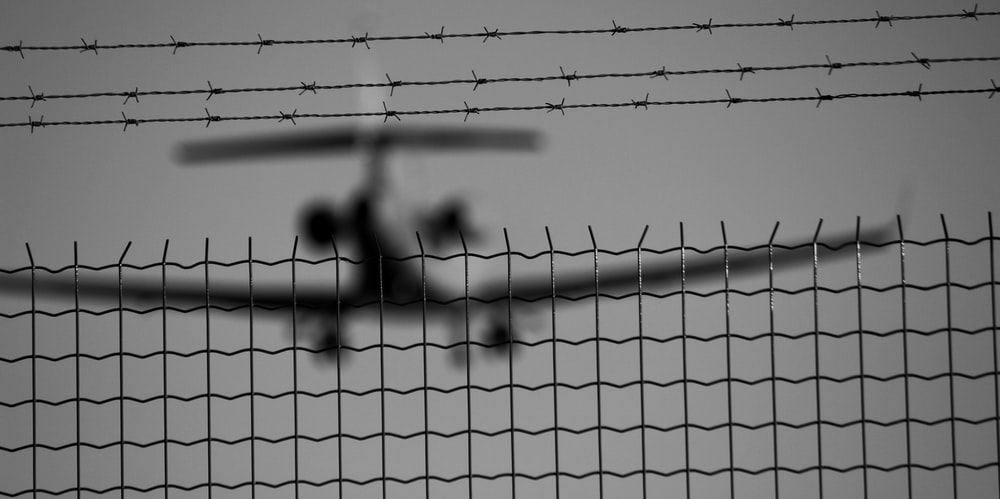 black metal fence in grayscale photography