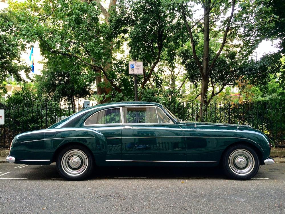 green sedan parked beside green tree during daytime