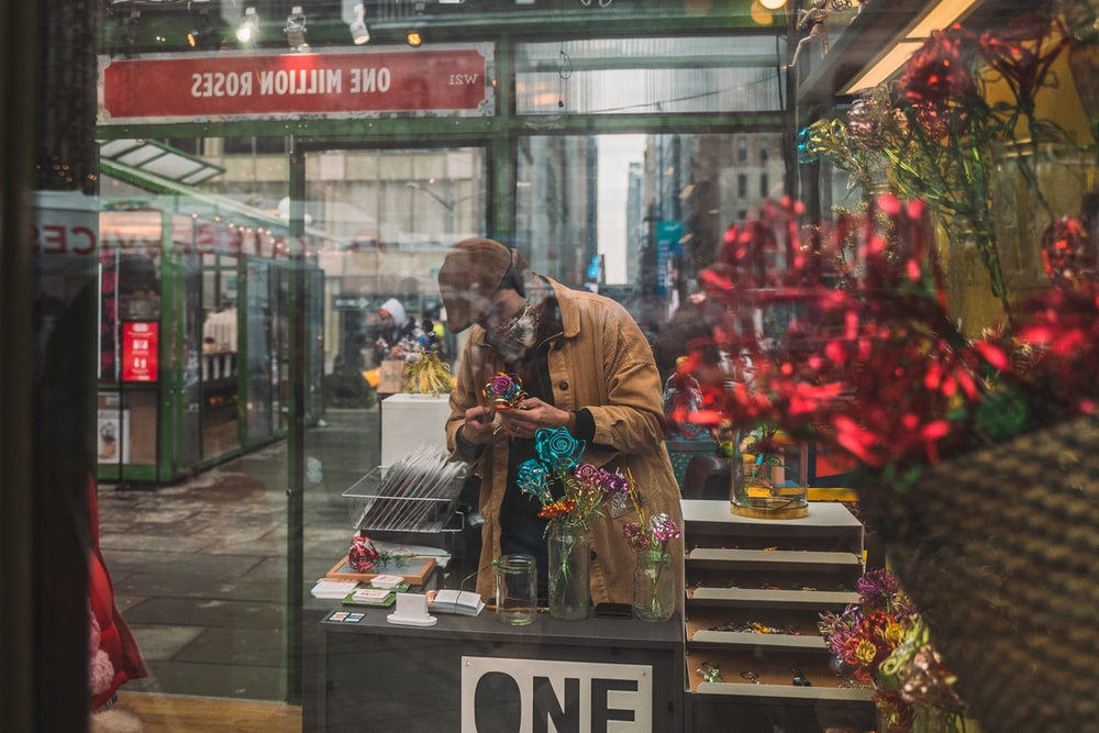 man in brown jacket standing in front of store