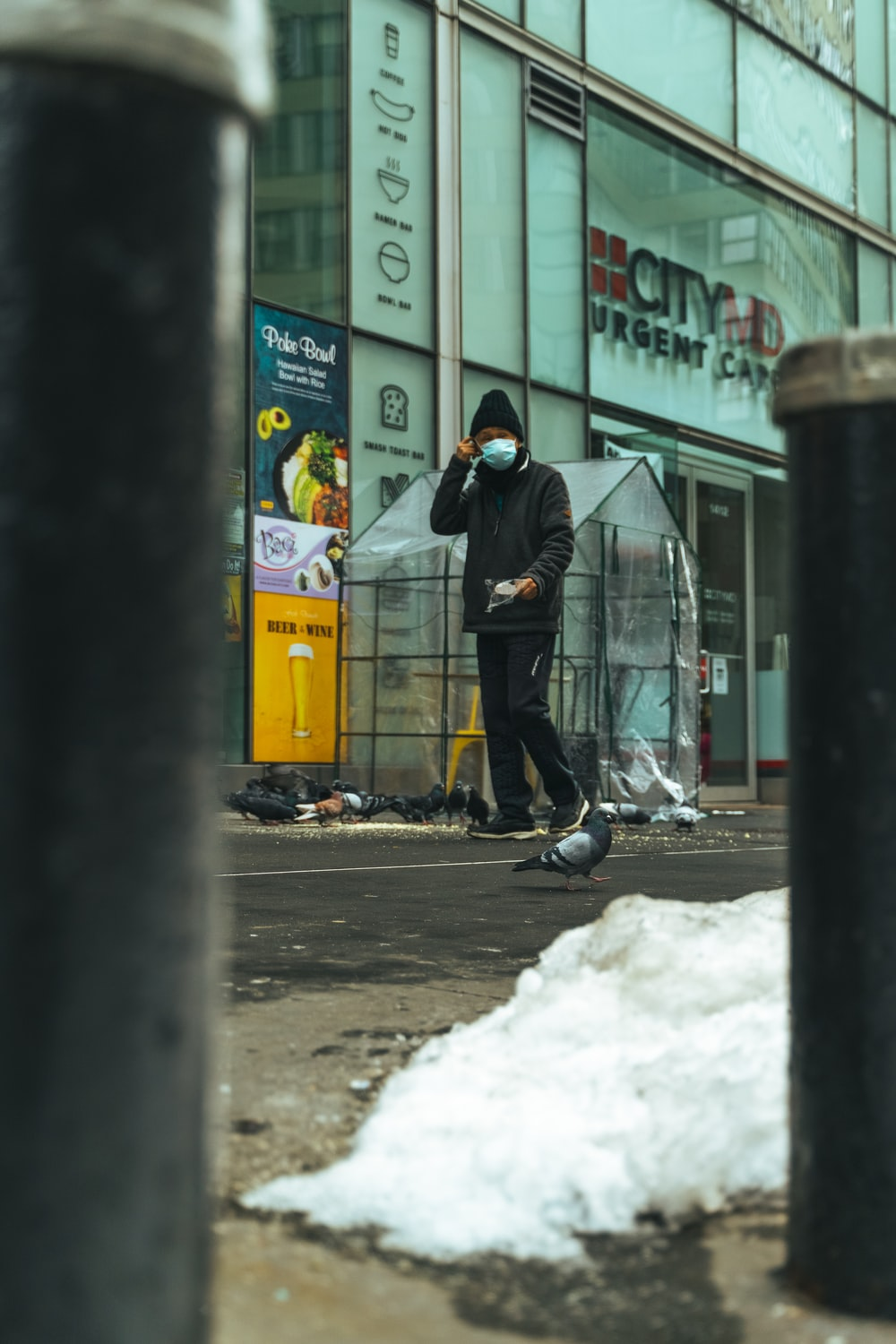 man in black jacket and black pants walking on snow covered road during daytime