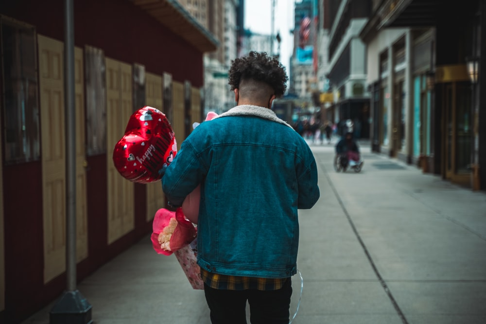 man in blue dress shirt and black pants holding red heart balloon