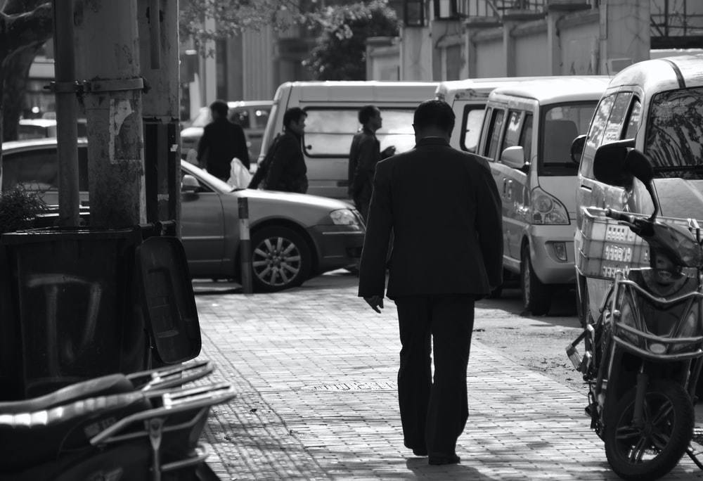 man in black coat standing near car in grayscale photography