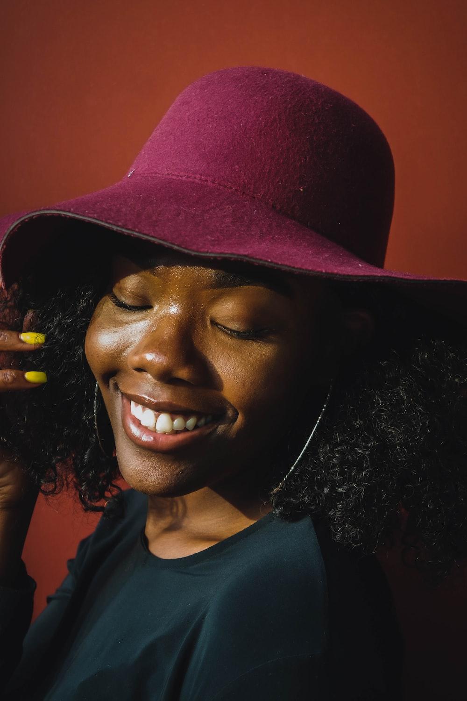 smiling woman in black shirt wearing brown hat