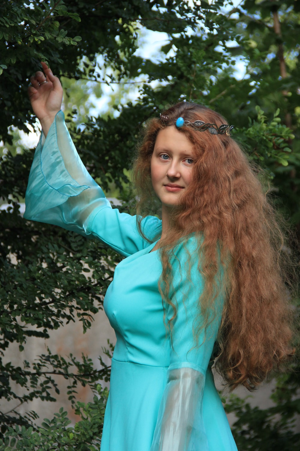woman in teal long sleeve shirt holding her hair