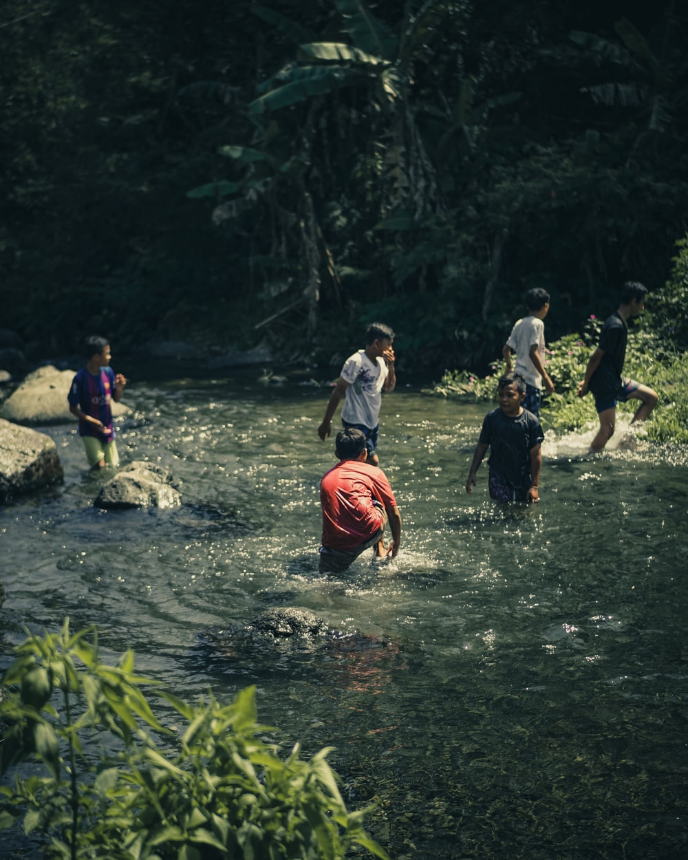 people standing on river during daytime