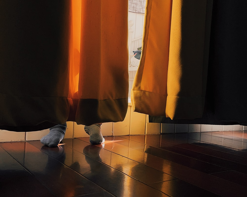 person in white shoes standing on brown floor tiles