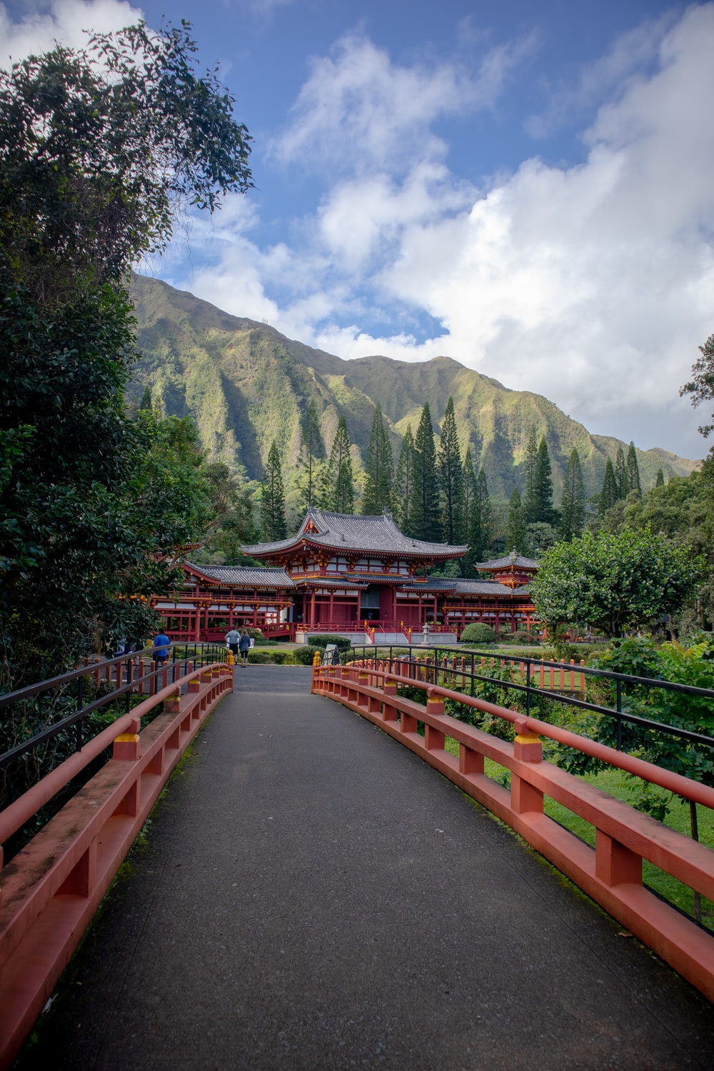 red and brown wooden bridge near green trees and mountain during daytime