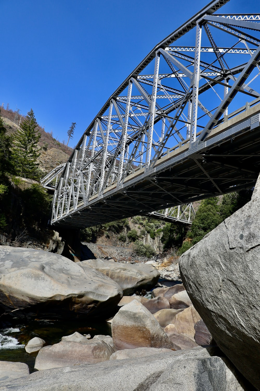 gray metal bridge over rocky river