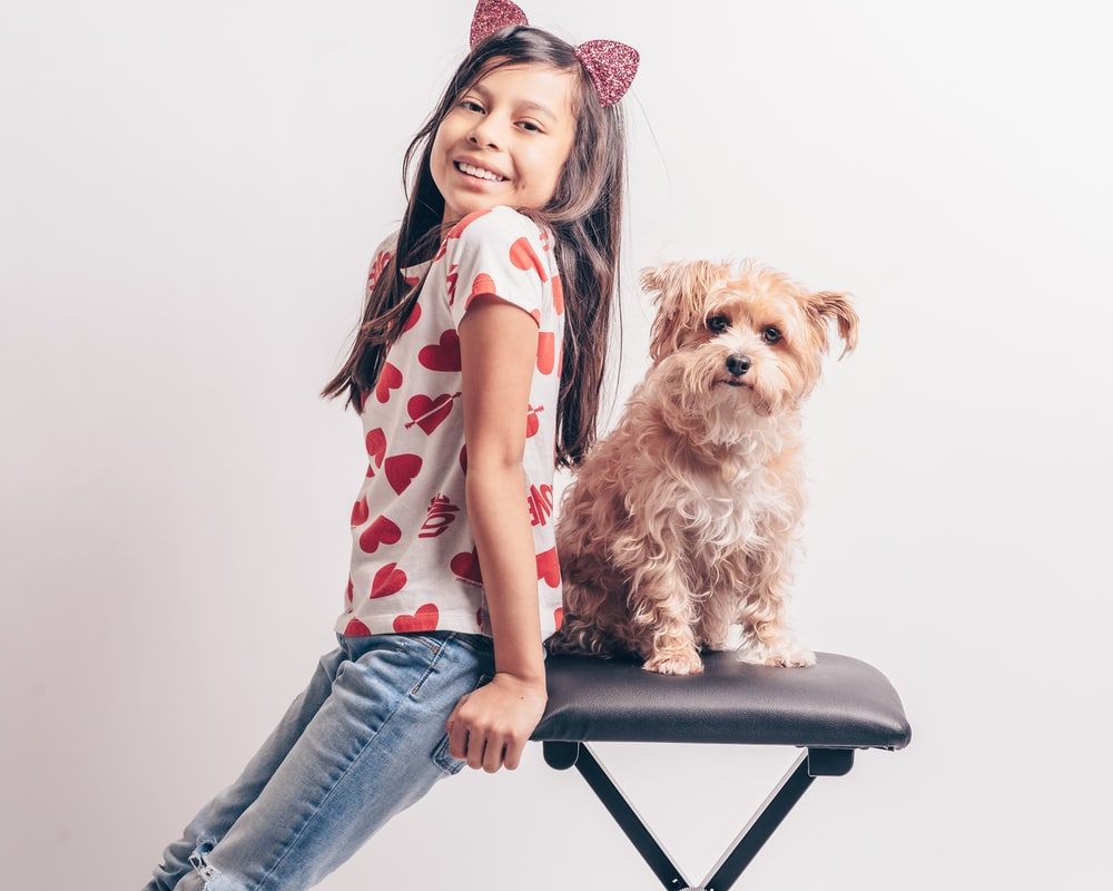 girl in pink and white polka dot shirt and blue denim jeans sitting on black chair