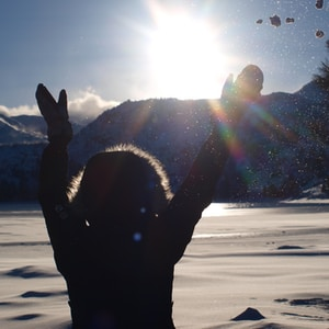 silhouette of man standing on snow covered ground during daytime