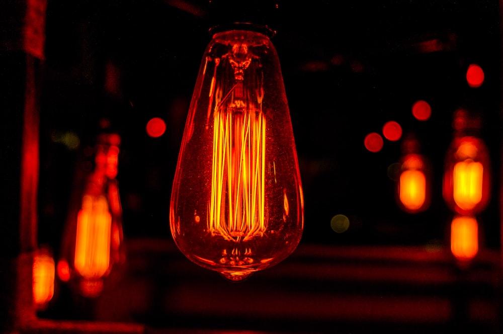 orange light bulb turned on in bokeh photography