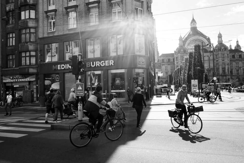 grayscale photo of people riding bicycles on road