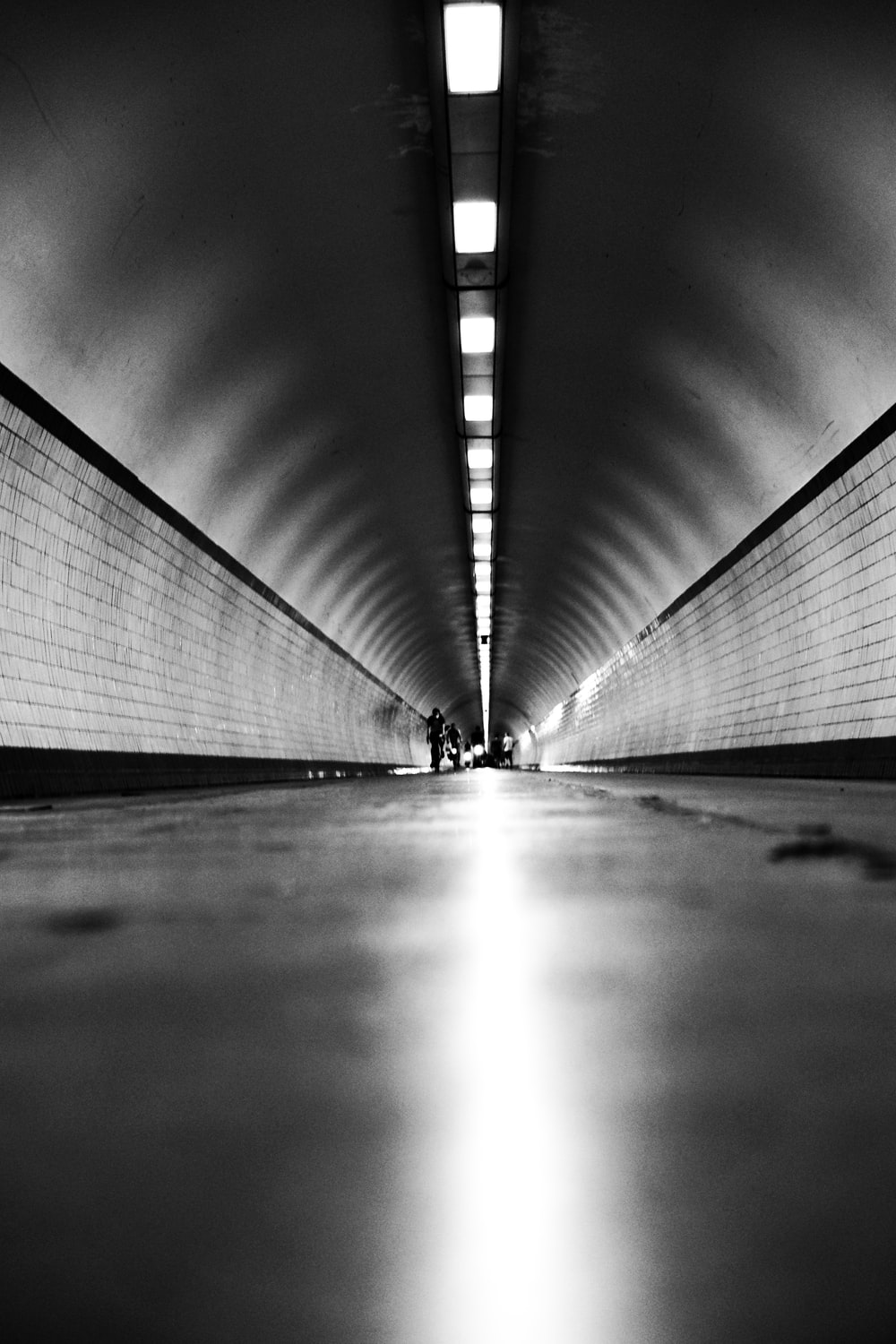 grayscale photo of a man walking on a hallway