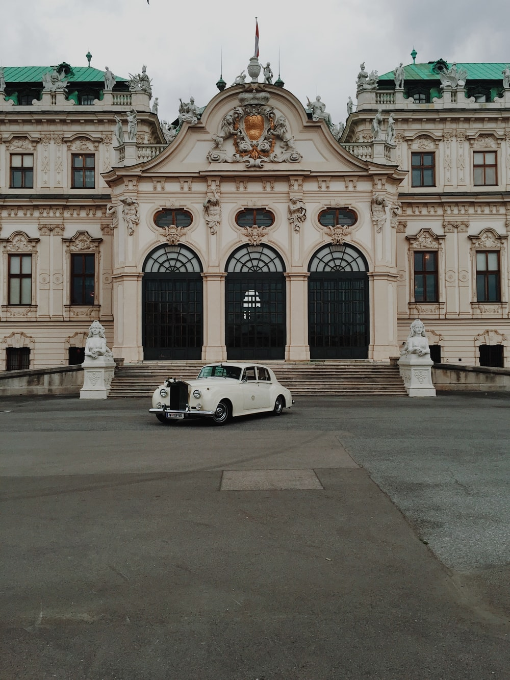 white coupe parked in front of white concrete building during daytime