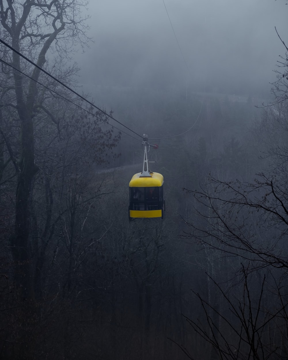 yellow and black cable car over the trees
