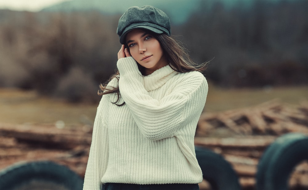 woman in white knit sweater and green knit cap