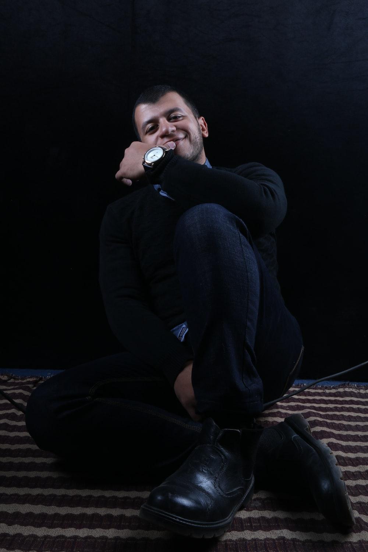 man in black long sleeve shirt and black pants sitting on brown concrete floor