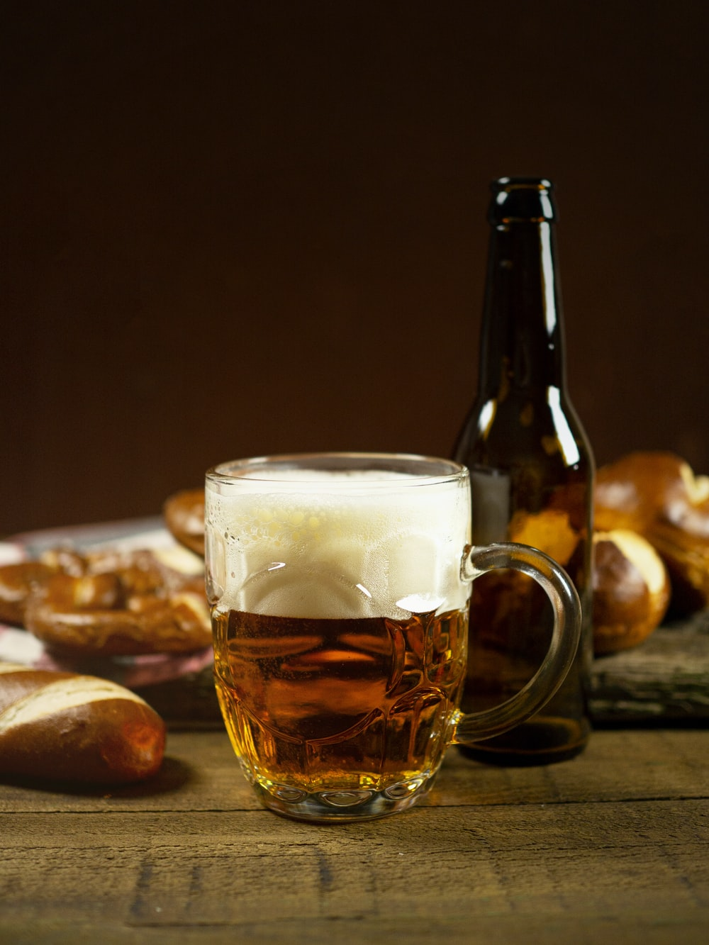 clear glass mug with beer on brown wooden table