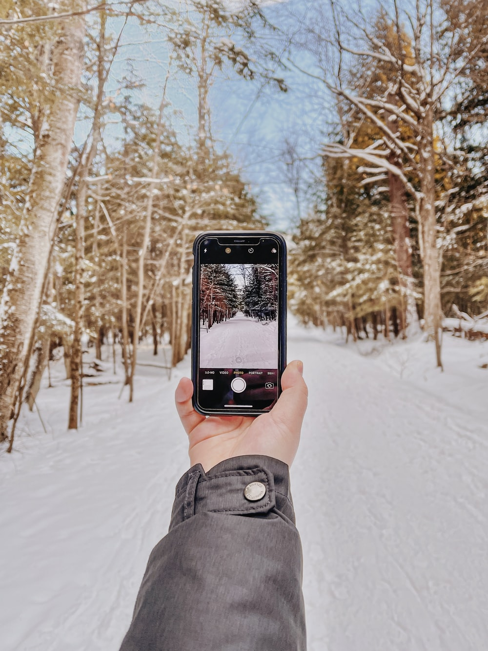 person holding black iphone 5 taking photo of snow covered ground