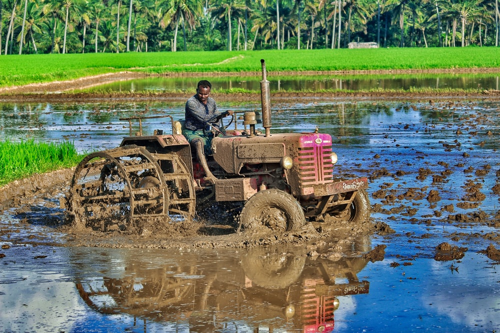 man in black jacket riding red tractor on river during daytime